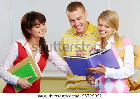 Portrait of three friends standing in classroom and discussing lessons