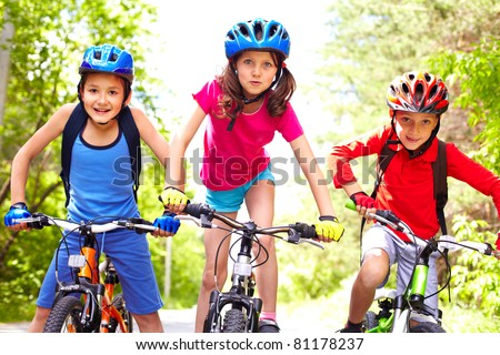Portrait of three little cyclists riding their bikes