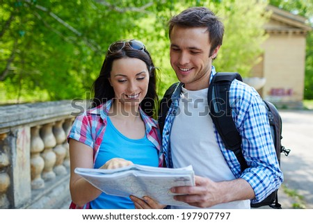 Portrait of travelers studying map of ancient town