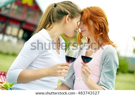 Portrait of two affectionate women with wine glasses outdoors