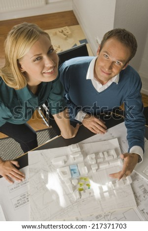 Portrait of two architects smiling in front of an architectural model