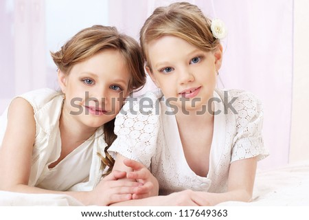 portrait of two beautiful little sisters looking at you
