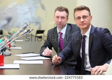 Portrait of two businessmen at negotiating table in conference hall