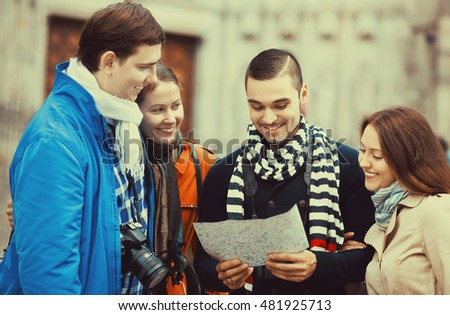 Portrait of two couples of smiling tourists reading city map and looking for correct way