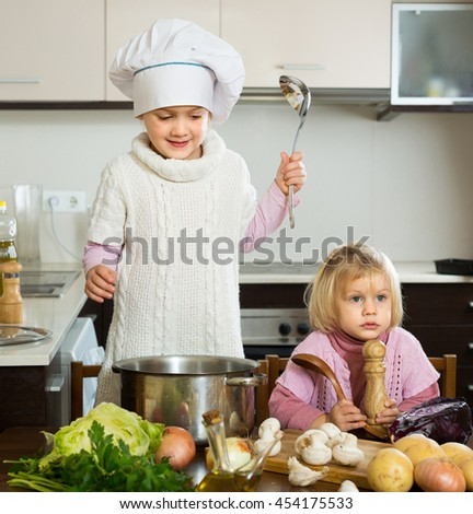 Portrait of two cute little girls with pot smiling at home kitchen