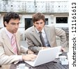 Portrait of two focused businessmen having a meeting in a coffee shop terrace in a classic city financial district with office buildings around them and using a laptop computer. - stock photo