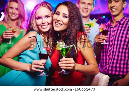 Portrait of two happy girlfriends with cocktails looking at camera at party