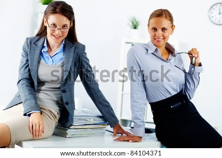 Portrait of two happy young businesswomen posing in office