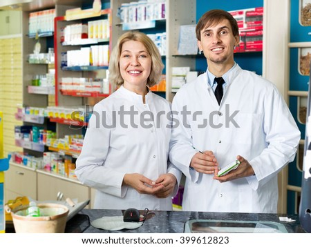 Portrait of two pleasant smiling pharmacists working in modern farmacy