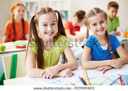 Portrait of two schoolchildren sitting at the desk and smiling at camera