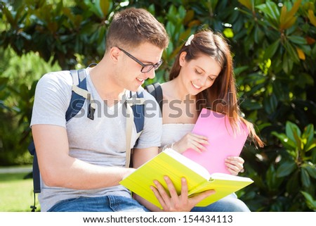 Portrait of two students talking in a park