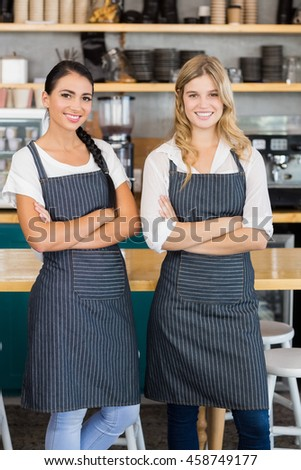 Portrait of two waitresses standing with arms crossed in cafe
