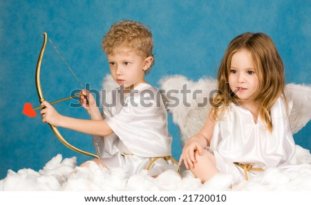 Portrait of two young angels sitting on the cloud