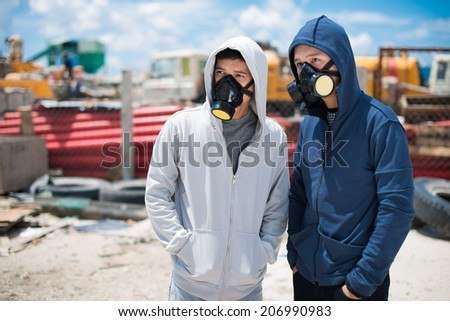Portrait of two young people in respirators standing outdoors