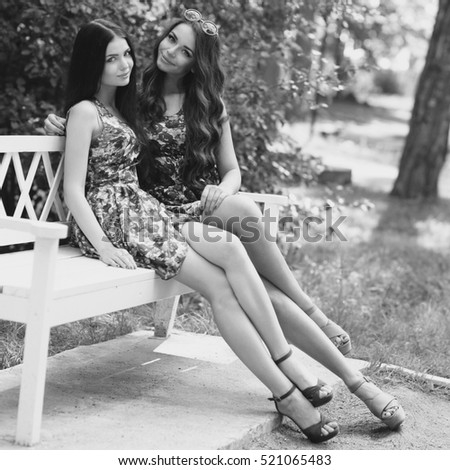 Portrait of two young woman sitting at bench in park. Cute friends in colorful dresses