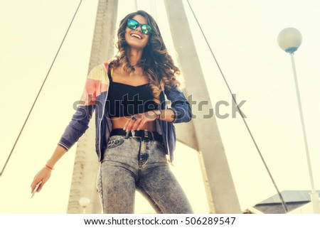 Portrait of very beautiful sports girl dancing on the street with mobile phone in hand, positive emotions, shining smile, enjoying her life, sports concept, wearing aviator glasses, attractive figure