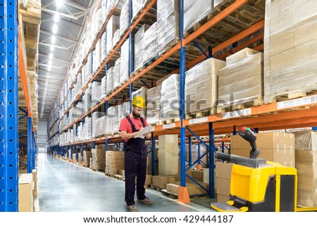 Portrait of Warehouse worker in a yellow helmet in a logistic center