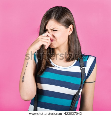 Portrait of woman covering nose with hand showing that something stinks against pink background