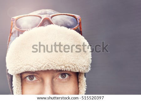 Portrait of woman in winter hat standing over grey background