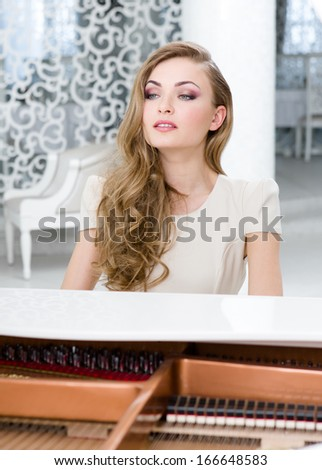 Portrait of woman sitting and playing piano. Concept of music and entertainment