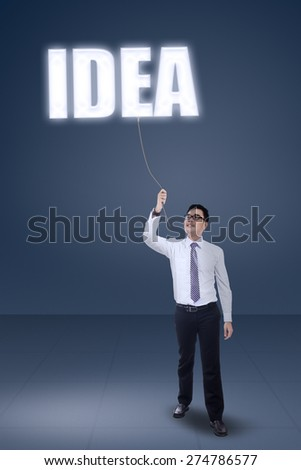 Portrait of young asian businessperson pulling an idea text, symbolizing he get in idea