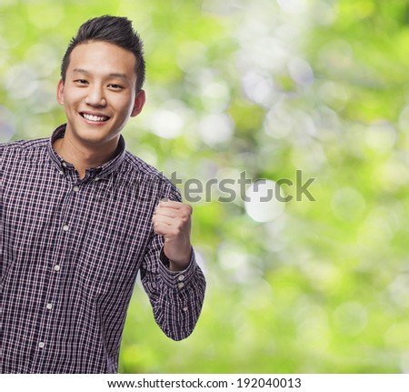portrait of young asian man celebrating something