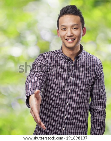 portrait of young asian man doing a welcome gesture