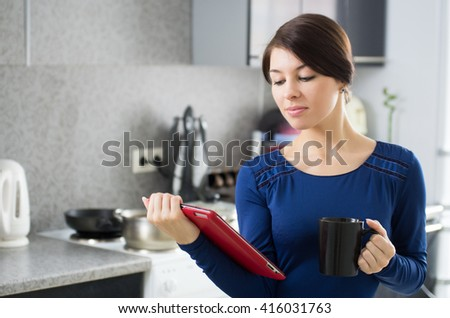 Portrait of young attractive caucasian brunette housewife at kitchen. Morning with cup of coffee and tablet pc.