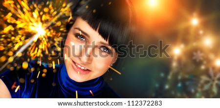 Portrait of young attractive celebrating woman holding sparkles
