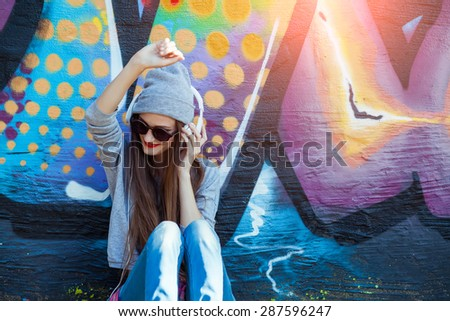 Portrait of Young attractive Teenager in Urban background Listening to Music with White Headphones