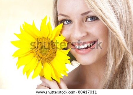 Portrait of young beautiful blond girl with stylish make-up and sunflower