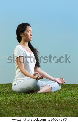 Portrait of young beautiful Chinese woman sitting meditating and in a yoga pose on grass