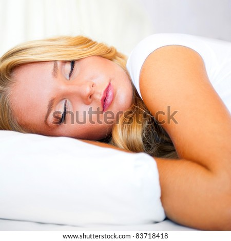 Portrait of young beautiful sleeping woman on bed at bedroom