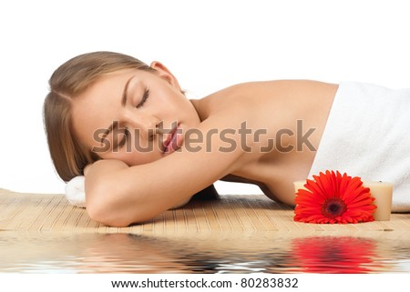 Portrait of young beautiful spa woman with closed eyes lying on bamboo mat in water