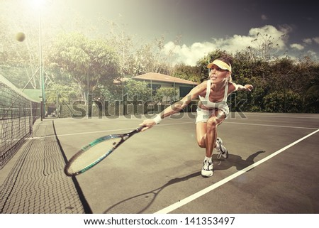 portrait of young beautiful woman playing tennis in summer environment