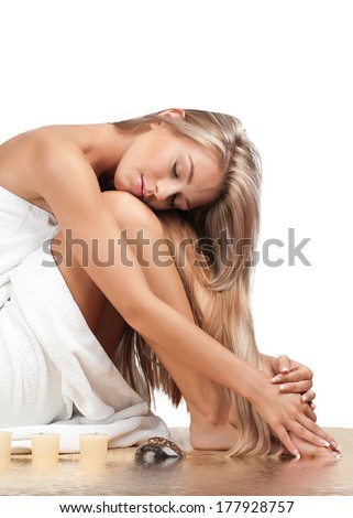 Portrait of young beautiful woman wearing towel and sitting on bamboo mat in water. Beauty treatment concept