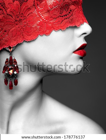 Portrait of young beautiful woman with red lacy ribbon on eyes