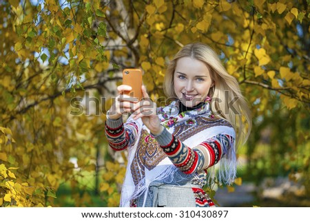 Portrait of young blonde woman talking on mobile phone in autumn park