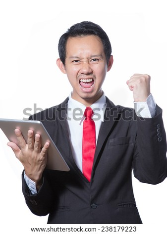 Portrait of young business man using tablet feeling success