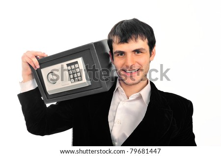 Portrait of young businessman holding metal safe. He looks confident and happy