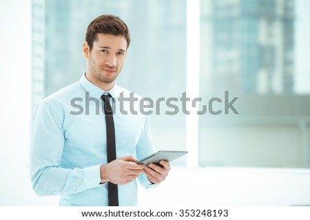 Portrait of young businessman in office with big window. Businessman using tablet computer and looking at camera