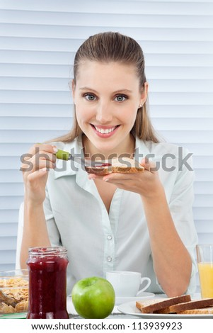 Portrait of young businesswoman applying jam on slice of bread while sitting at table with breakfast