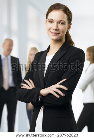 Portrait of young businesswoman standing at office with arms crossed while her colleagues consulting at background.