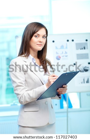 Portrait of young businesswoman with clipboard looking at camera in office