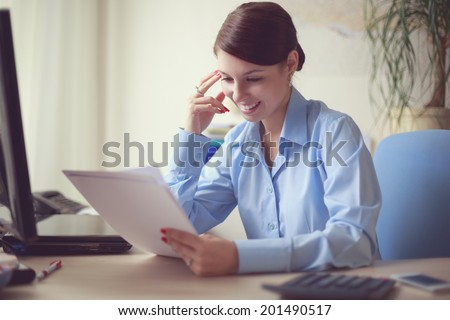 Portrait of young caucasian business woman in blue shirt at her office reading the documents.