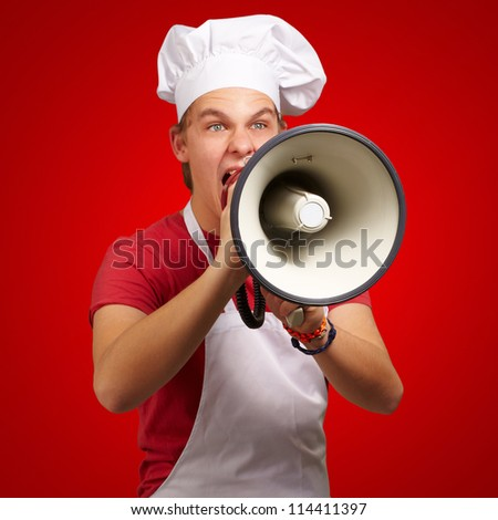 portrait of young cook man screaming with megaphone over red background