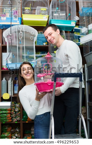 Portrait of young couple purchasing bird cage in petshop