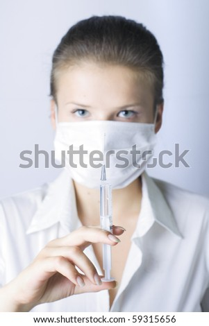 Portrait of young doctor with mask and syringe