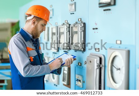 Portrait of young engineer taking notes at control room in factory