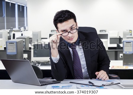 Portrait of young entrepreneur sitting in the office and look at the camera seriously while wearing formal suit